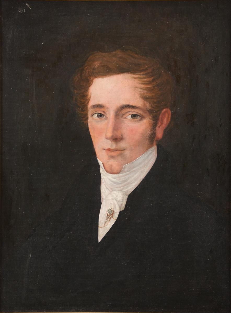 Portrett av ung mann, venstrevendt, foroverbørstet hår, mørk drakt med hvitt halsbind med brosje og lang nål.