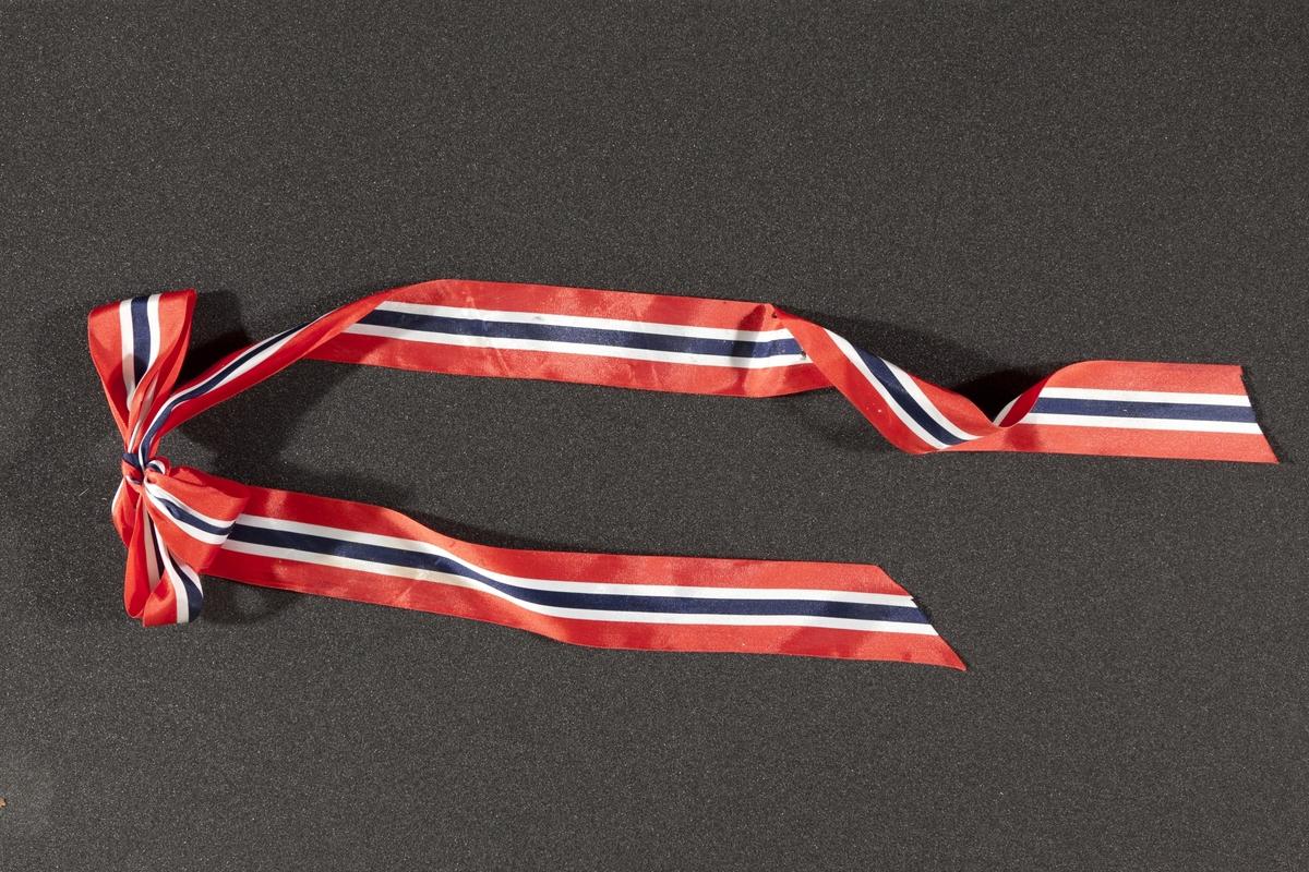 Sløyfe med flaggets farger innsamlet etter terrorhandlingen 22. juli 2011 fra minnesmarkeringene i Lillestrøm.   Båndet er knyttet som en sløyfe men den har en ekstra løkke til å holde sammen f. eks. en blomsterbukett. Den ene enden i sløfen er lenger enn det andre. Dette lengste båndet har fått noe klister på seg. Sløyfebåndet har noen merker og bretter. Båndet er skråklippet i endene.