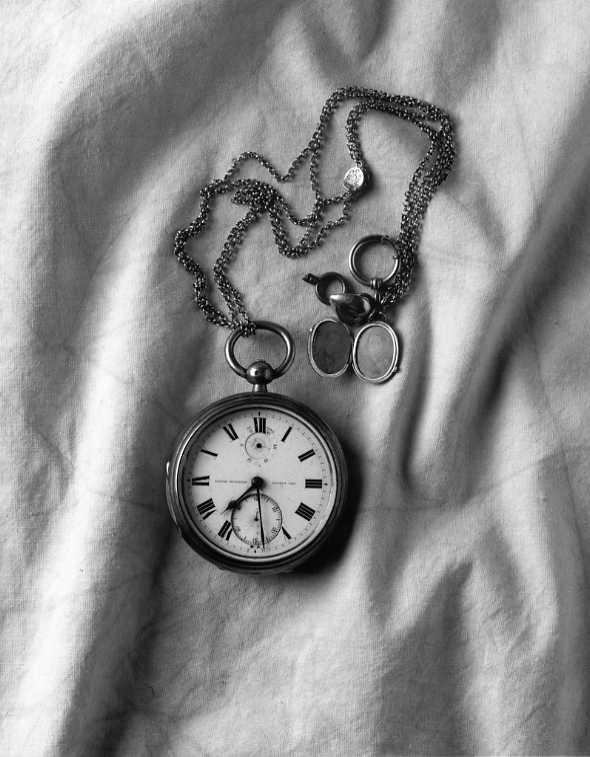 S A Andrées kronometer i kedja med berlock som innehåller fotografi på hans mamma och pappa. Återfanns på Vitön 1930.