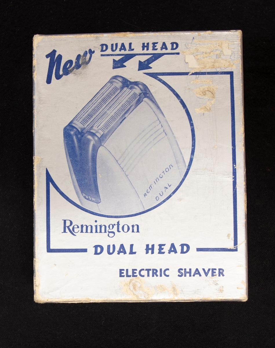 Elektrisk rakapparat av märket Remington i originalask.   Rakapparat med elsladd. I pappförpackningen ligger en läderväska som stängs med tryckknapp. I denna läderväska ligger sladd och rakapparat. på lockets insida står skrivet med bläckpenna: Ericsson, Tel V-ås 32689  En papperslapp med garanti finns i asken, som är utfärdat 13 december 1947. Även kvittot, som visar att rakapparaten inköpts samma datum i Västerås.  Asken visar en bild på rakapparatens huvud samt texten: New Dual Head, Remington, Dual Head, Electric Shaver  Leif Erixon såld rakapparater i sin affär. Denna är dock äldre och är såld redan 1947. Troligen har Erixon fått den och har sedan haft den i hans lilla historiehörna i salongen.