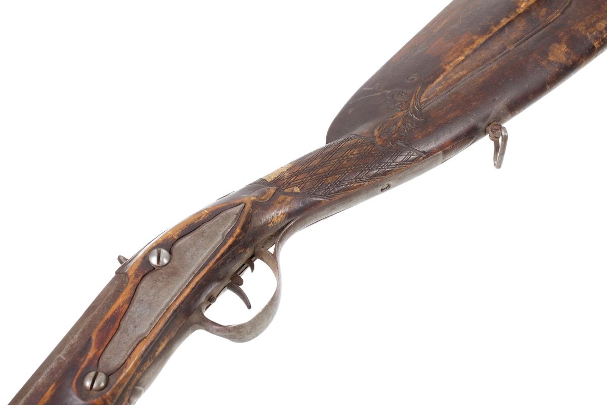Flintlåsgevär sekundärt ombyggt till slaglås. Det är försett med helstock och har näsbeslag av horn. Laddstocken sitter i tre rörkor av järn i en laddstocksränna. Kolvens bakplåt är tillverkad av järn och går upp över kolvryggen och avslutas med en spets. Kindstödt på kolvens vänstersida har en skuren bladdekor i framkanten. Kolvhalsen har ett skuret rutmönster, och en rembygel sitter i kolvens underkant. Det främre rembeslaget sitter i mellanrörkan och är skruvat i kolvens undersida. Pipan är rund med en åttakantig avslutning. Vid svansskruven sitter ett filat gropsikte, och ca 50 mm. bakom mynningen sitter ett avlångt mässingskorn. Pipan har åtta räfflor och en innerdiameter på 16 mm. Inskrivet i huvudkatalog 1885.