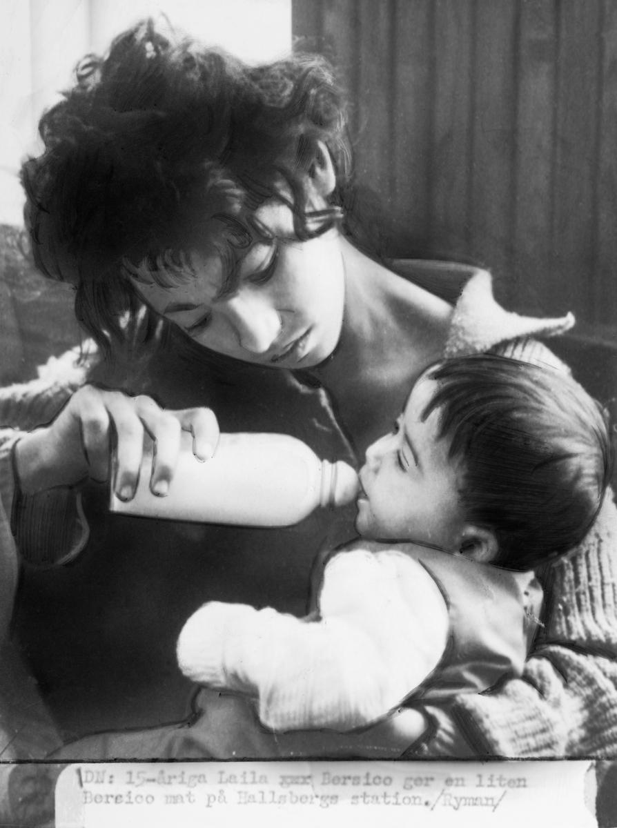 En femtonårig flicka matar ett litet barn med nappflaska. Bilden är tagen på stationen i Hallsberg.