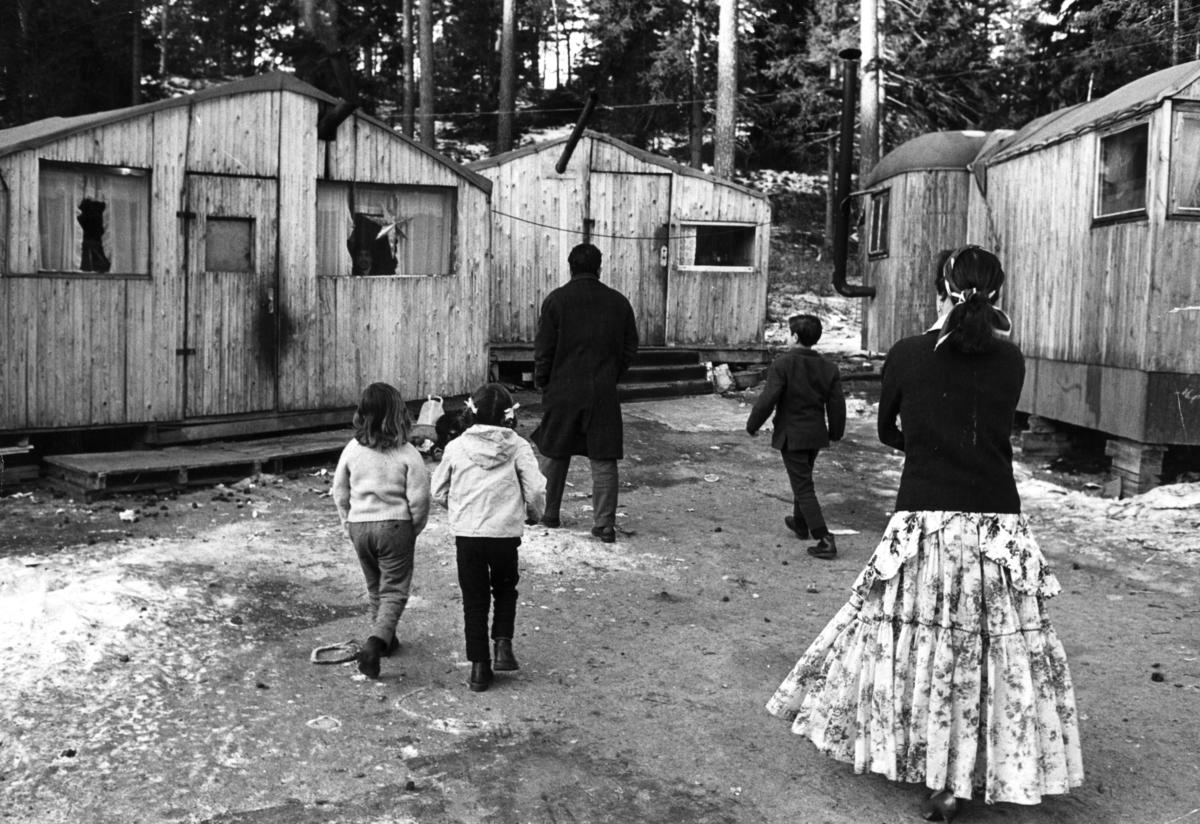 """Bilden är antagligen tagen i det romska lägret på Ekstubben.  Lägerplatsen låg i Skarpnäck söder om Stockholm, i nuvarande Flatens naturområde, på en plats där det i dag ligger en motorbana. Lägret var samtida med Skarpnäckslägret några kilometer bort och iordningställdes 1959 av Stockholms stad för svenska romer i kommunen som ännu inte hade fast bostad.  Fastighetskontoret i Stockholms stad hade i en kommunal utredning 1955–1957 kommit fram till förslaget att iordningställa särskilda lägerplatser. Lägren skulle finnas under en övergångsperiod innan fasta bostäder ordnats, men i realiteten drog bostadsfrågan ut på tiden och lägren blev kvar i fem år. I Ekstubben bodde människor under enkla förhållanden, inledningsvis i tält och vagnar och efter hand också i egenbyggda baracker och stugor kring en öppen yta. Lägret försågs med el och vatten, torrtoaletter samt sophämtning. Ekstubben stod färdig för inflyttning 15 mars 1960.  I reportaget """"Vagabond eller vanlig människa?"""" av Roland Hjelte och Karl Axel Sjöblom som sändes i SVT i mars 1963 skildras livet i dessa läger under vintern 1963. I intervjuerna med de boende i lägret framhålls det akuta önskemålet om fast bostad. I lägret bodde det året 15-20 familjer och reportern berättar att människor har bott här flera år i väntan på att Stockholms stad ska lösa bostadsproblemet. Det är vinter, snön har fallit och vissa nätter gick temperaturen under nollstrecket inne i husvagnarna. En man berättar att han är uppe hela nätterna för att elda i kaminen. Han säger till reportern: """"När alla andra fått bekvämligheter ska vi också ha det. Vi kan inte ha det så här!"""". Det skulle dröja till maj 1964 innan de sista av de svenska romerna flyttade från Ekstubben. Senare användes Ekstubben dock fortsatt som lägerplats för romer som kommit till Sverige från andra delar av Europa."""