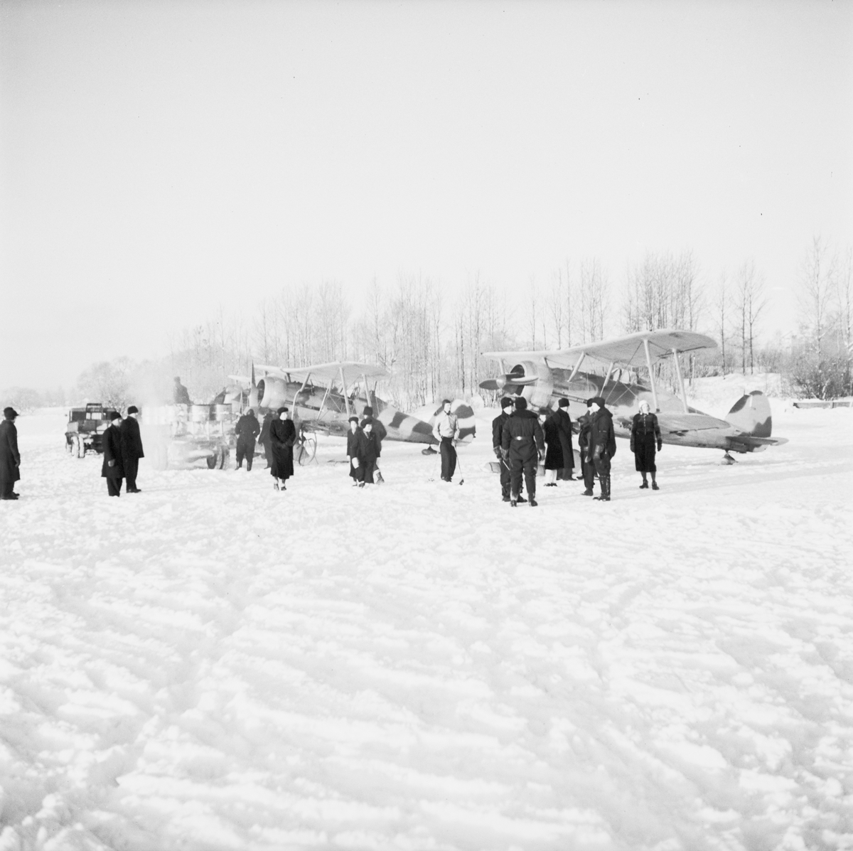 Militärer och Ljusdalsbor samlade på flygfältet på Kyrksjöns is i Ljusdal den 1 januari 1940. I bakgrunden står två flygplan Gloster Gladiator. Flygplanen flög senare vidare till Svenska frivilligkåren i Finland, F 19.