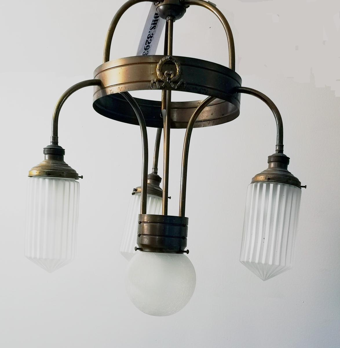 Lysekrune med kulefora kuppel i midten, pluss 3 lysarmar med sylinder/riflerforma kupplar. Alle kupplane i matt glas. Dekor i nyklassisisme Lysekrune er i nyklassisisme.