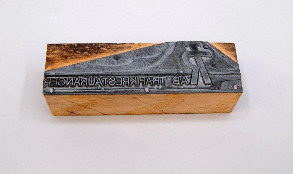 """Rektangulär kliché av grå metall monterad på en rektangulär träkloss. Klichéns övre hörn är beskurna. Den har texten: """"TR AB TRAFIKRESTAURANGER"""" i relief. Under texten finns en linje i relief."""