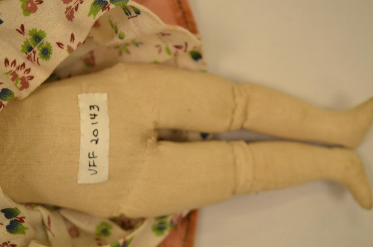Dokke med porselen-hovud. Kroppen er stoppa og trekt med ubleikt bomullstøy.  Dokka har blomstra kjole og rosa fløyelskåpe. Brunt påsydd hår. Kleda er maskinsydde.