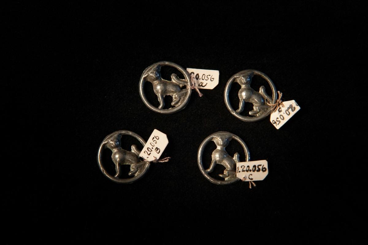 En s.k. snörmalja i genombrutet tennmed hundliknande dekor inom en ring.