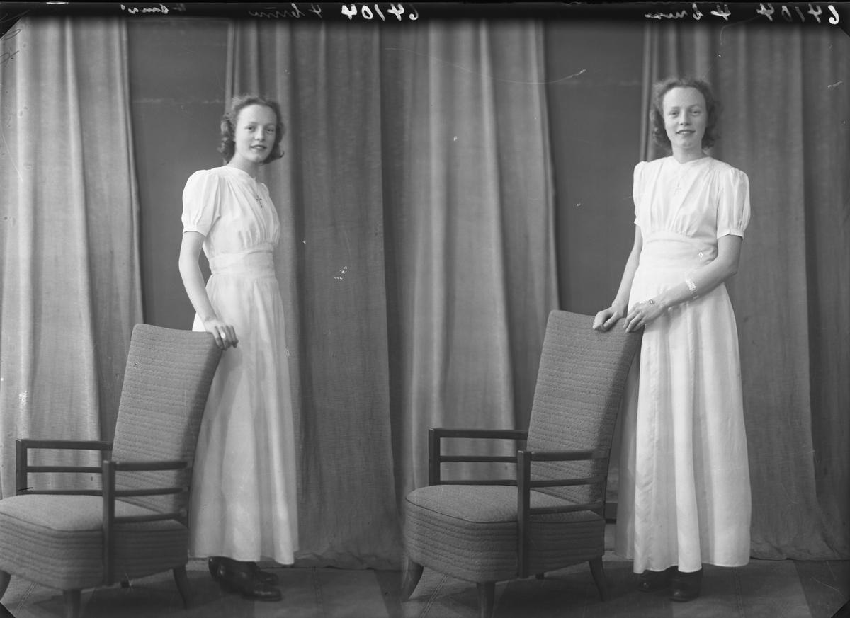Portrett. Ung kvinne i lang lys kjole. Poserer med en stol. Konfirmant. Bestilt av Ingrid Johansen. Grenseplas 10