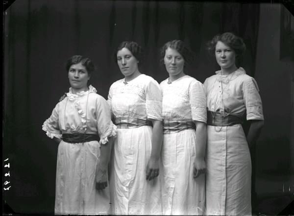 35650678f5fb Ateljébild av fyra kvinnor (syskon?) i ljusa klänningar med breda  sidenskärp; de två i mitten ...