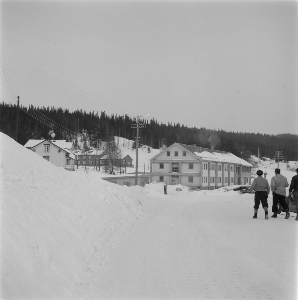 Herredshuset i Hattfjelldal. Vinter, personer som går på veien, noe av bebyggelsen ved siden av.