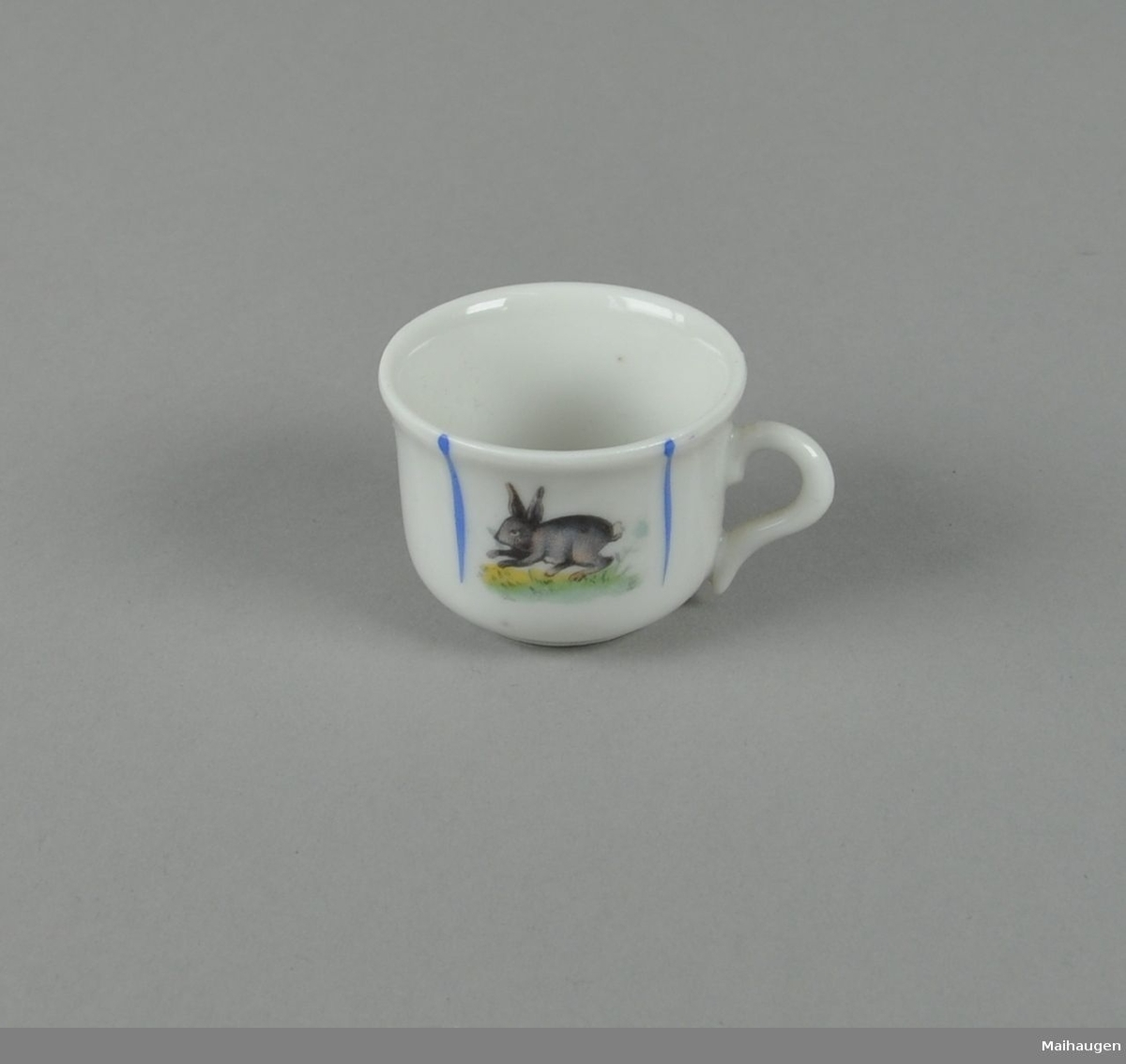 Hvit kopp av glassert keramikk, med malt dekor av nedovergående blå striper og hare i midten.
