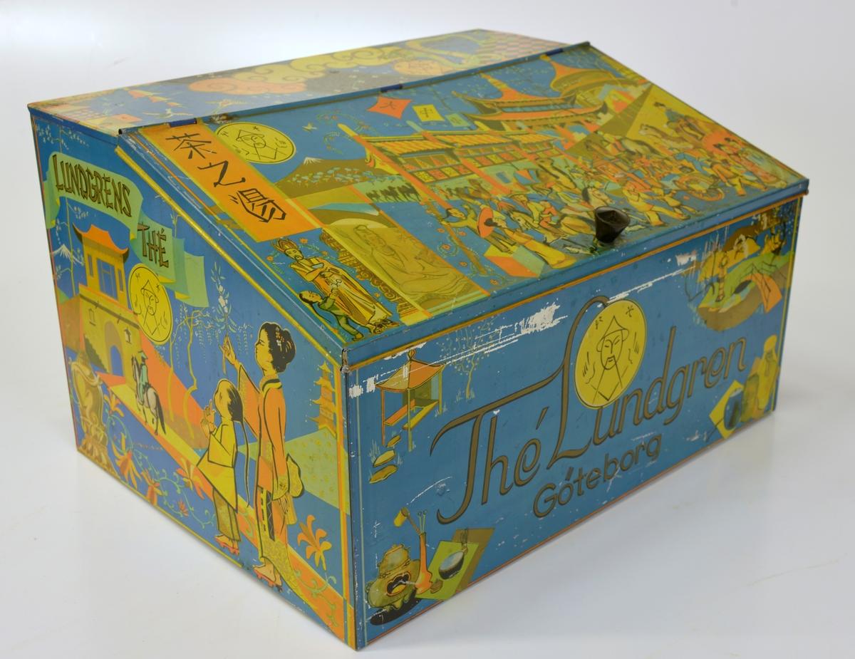 """Dekorerad med färgglada bilder som föreställer kinesiska miljöer. Det snedställda locket pryds av en myllrande gatuscen. Text """"Thé Lundgren Göteborg Lundgrens thé"""".  Från Arne Ekströms handelsmuseum."""