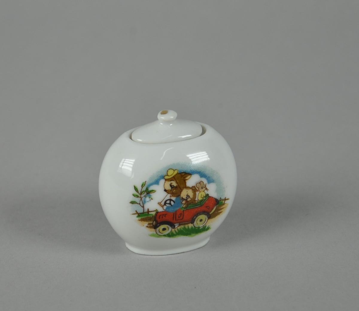 Skål av glassert keramikk. Hvit farge, med farget motiv av harer og mus i rød bil. Skålen har lokk.