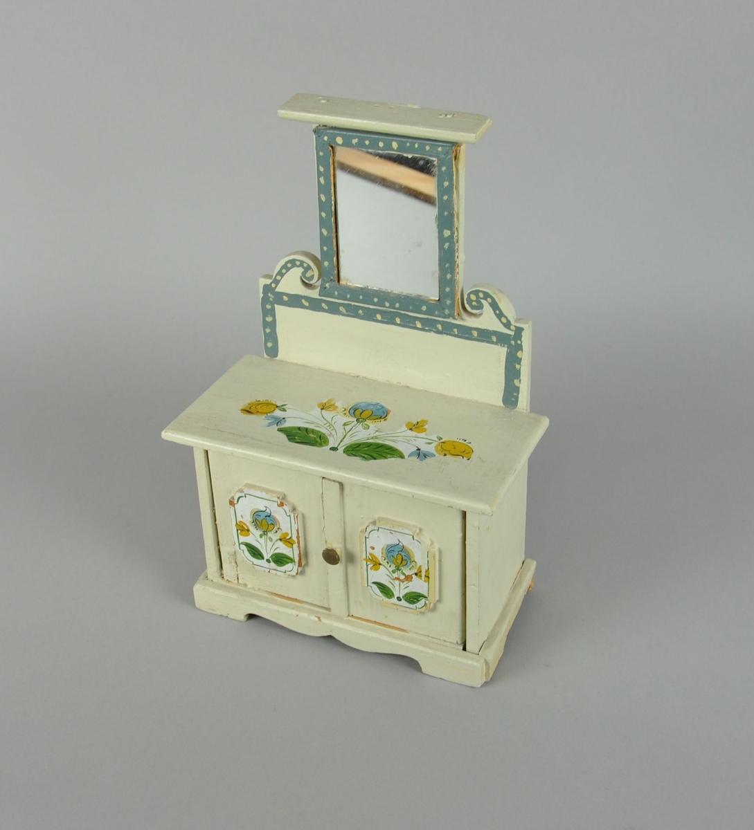Lekeskap av tre, med speil. Skapet er sveifet ved bunnen og har blåmalt dekor med hvite prikker. To funksjonelle dører på framsiden, og i skapet er det ni små bøker.