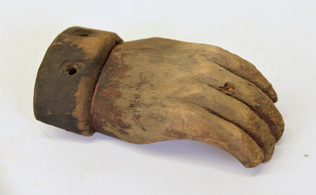 """Dörrhandtag snidad i form av en hand. Har suttit på en dörr till en lokal som förr varit """"hemlighus"""" inom fastigheten Nr 1-4 Kv. Alströmer, Alingsås."""