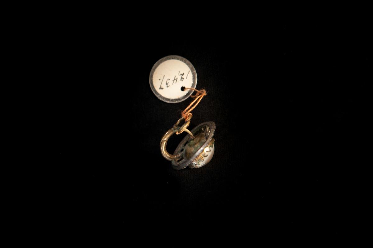 """Ovalt örhänge av delvis genombruten metall, besatt med slipade stålbriljanter (s.k. """"Falubriljanter"""") och en stor pärla i mitten. Ligger i gulbrun pappask (JM.12437:2)."""