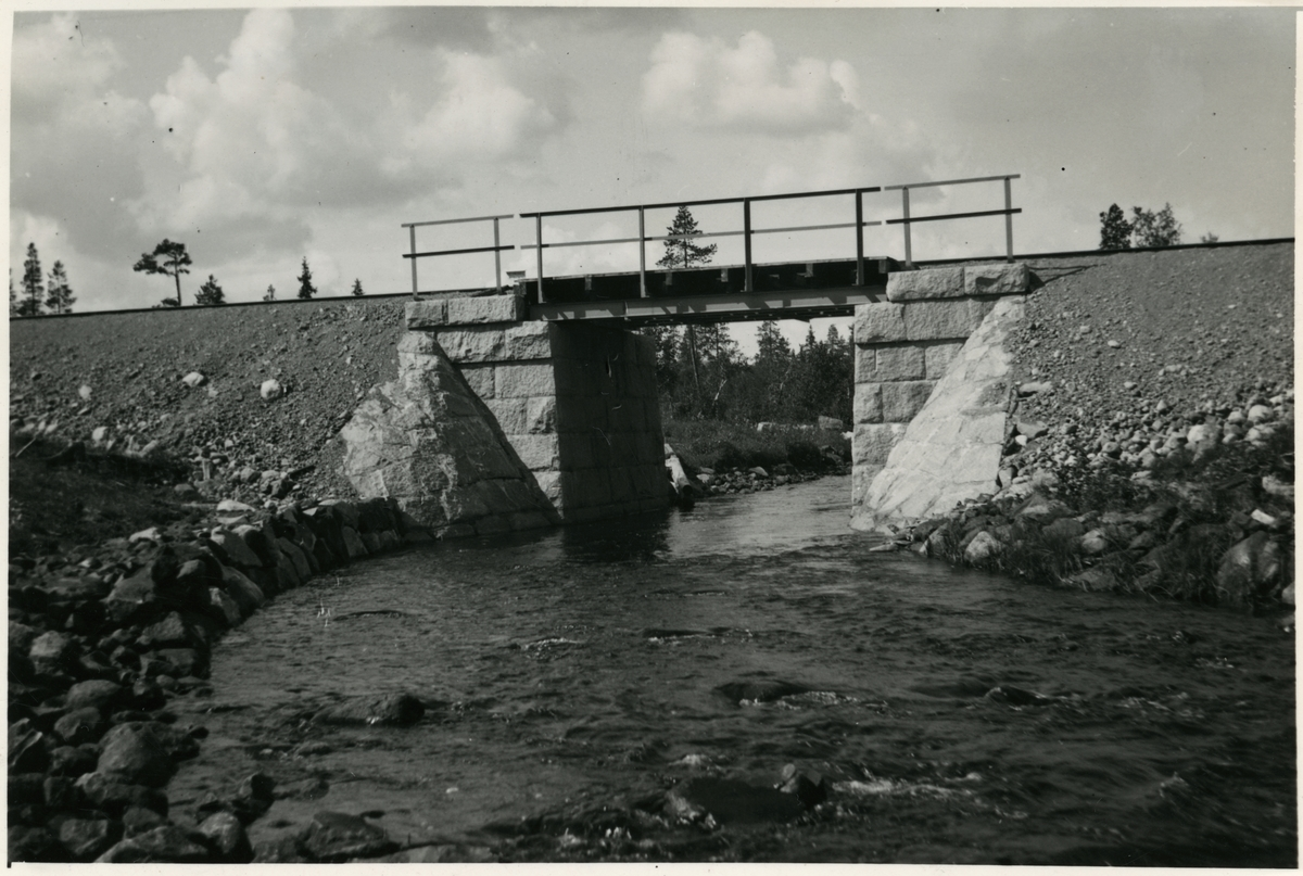 Järnvägsbro över Hundträskbäcken. Järnvägen som går genom Jokkmokks område sträcker sig över många vattendrag, bäckar, åar och älvar. Broarna som byggdes över de anpassades till terrängen. De var framförallt funktionella men, deras utseende gick från väldigt enkla, grovhuggna till sublima, estetiskt utformade valvbroar.