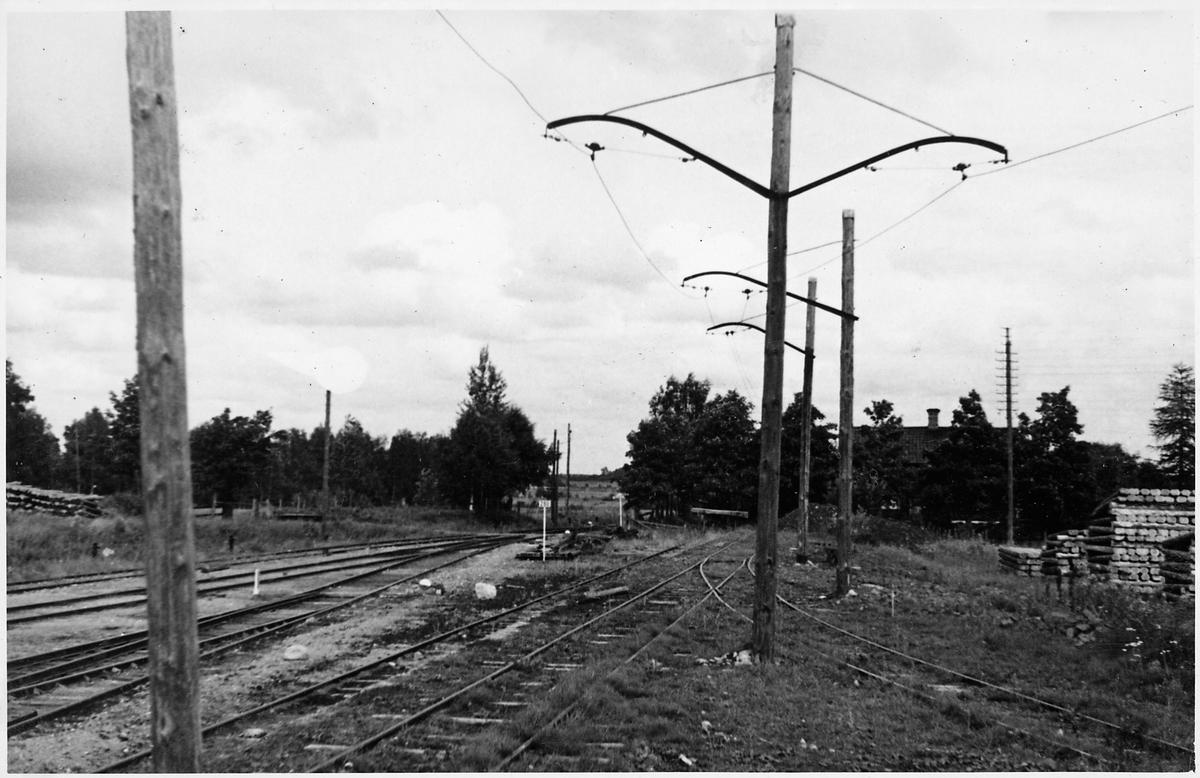 Till höger syns den elektrifierade smalspårsbanan Stockås-Mullhyttemo mellan Stockås torvströfabrik och Mullhyttemo station. Till vänster ser vi bangården vid Mullhyttemo station. Bilden tagen i samband med den stundande elektrifieringen av sträckan mellan Örebro-Svartå.