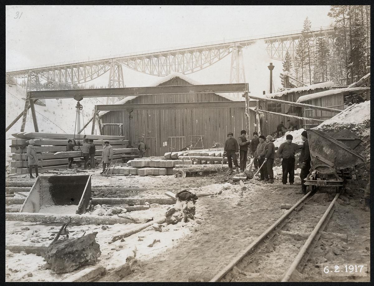 Pålupplag utanför verkstad, under under byggnationen av Tallbergsbron över Öre älv. I bakgrunden syns den äldre bron.
