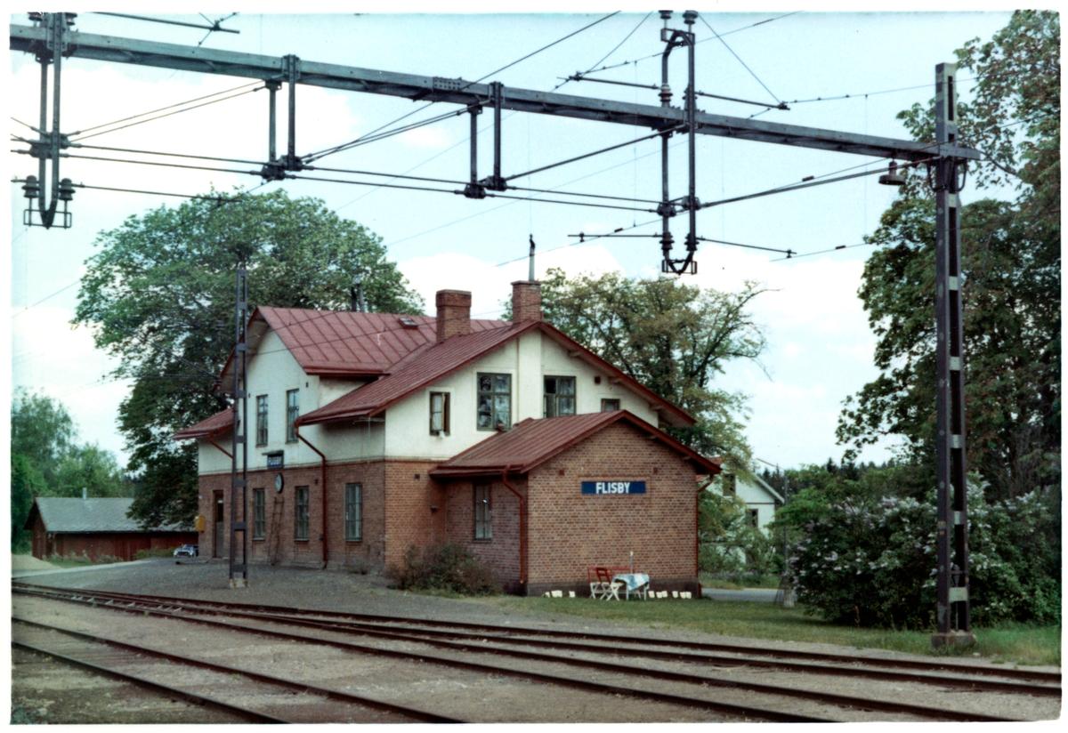 Litet stationshus av sten.Stationen nedlagd. Men vid banans upprustning 1994 - 1995 blev linjeplatserna FLISBY NORRA, FLISBY MELLAN och FLISBY SÖDRA 1994-10-01 åter igen uppgraderade till stationen FLISBY Stationen anlades 1873.