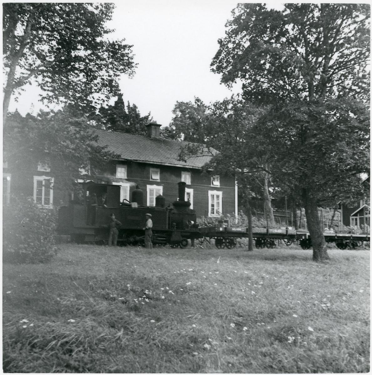 """Bruksgatan i Lotorp, ånglok med tåg. Detta är troligen Finspong Lotorps Järnväg, FgLpJ lok 2 """"Nordiska""""."""