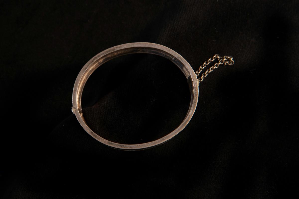 En stel armring av silver med graverad blomdekor (blåklockor). Lås med säkerhetskedja.Stämplar på låset.