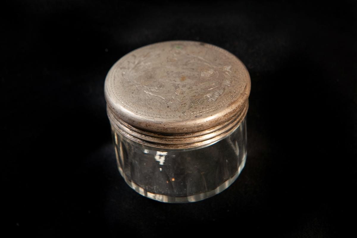 """En rund dosa i olivslipat glas. Runt lock av metall, graverat med blomslingor och namn: """"Wivi"""" på ett band.Locket troligen gjort av nickel eller nysilver. Ostämplat."""