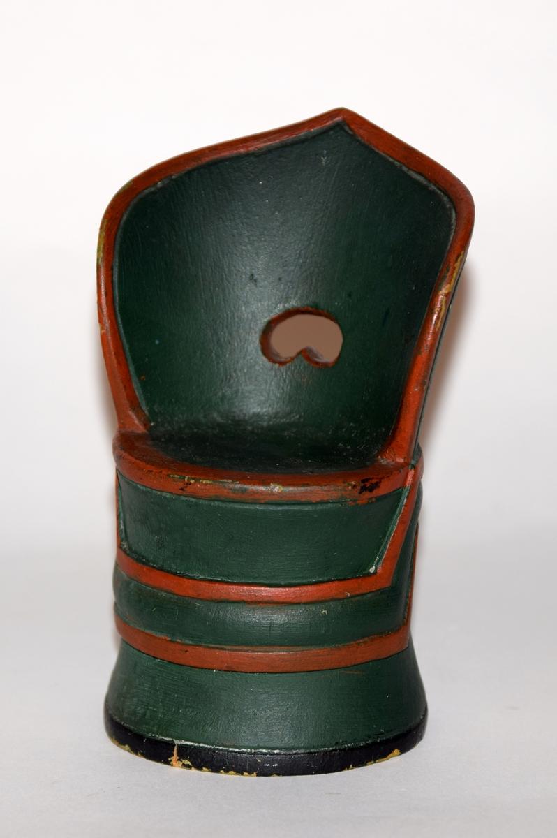 Skåret, stilisert kant på ryggen, omvendt  *23 hjerte skåret ut i ryggen. Bord m/sirkler på stolen. Stolen kan fungere som skrin fordi setet er løst. Stolen har opprinnelig vært gul og grønn. Gave til Hulda Garborg?