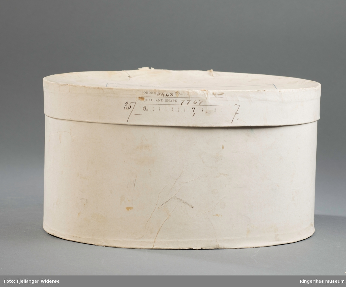 """A: Flosshatt i flott kvalitet, bred brem med svak bøy på sidene. Kantebånd langs bremmen. Ripsbånd med enkel liggende sløyfe festet i overgangen mellom brem og hatteform. Bredt for i tynt skinn montert på innsiden, """"svettekant"""", og for i tynn silke på resten av hatteformen og i bunnen.  Hullsøm i skinnet på innsiden, trukket silkebånd og sløyfe.   B: Original hatteboks med lokk, oval form og tilpasset flosshatten i akkurat riktig størrelse. Etikett til utfylling midt på lokket og oppgitt størrelse på flosshatten på sideflaten. Lokket er festet til boksen med tynn hyssing på bakre sideflate.   C: To stk. elastisk og gjennomsikltlig tekstil, klippet og sydd sammen som et pannebånd."""