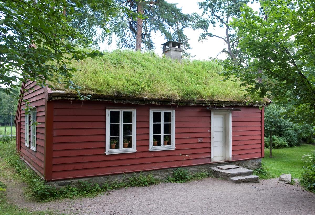 """1866 - 1867 Skolestua er et typisk landsens skolehus, slik det skulle være etter loven om """"fast skole"""" av 1860. Det er tre rom i skolehuset; selve skolestua, gang og et lite rom for læreren. En innebygd sval går langs baksiden. Huset hadde opprinnelig torvtak, men fikk senere tegltak. Skolestua er innredet etter beskrivelse fra eldre mennesker i Natås, som husket stua fra ca 1900 til 1923, da lærer Ole Bjørnvoll kom til skolen. Han var ung og brakte med seg nye impulser, og han hadde lært at læreren skulle sitte - ikke stå - bak kateteret. Tavlen, Bibelen, kassen med blekkhus, spyttebakken, globusen og de fleste kartene har fulgt med skollehuset, likeså skapet og bordet i lærerens rom. De små stolene, to av skolepultene og parafinlampen kommer fra distriktet, og svarer til de som stod i skolestua. De fleste pultene er antakelig fra 1920-årene.  Norsk folkemuseums guidebok,  1996"""