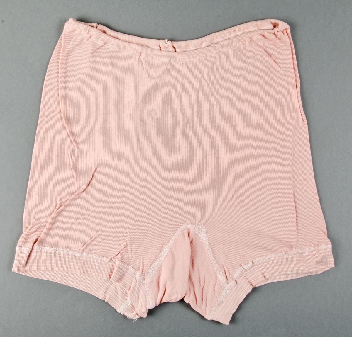 Underbyxor av rosa bomullstrikå. Maskinsydda. Resår i midjan. Hål vid midjan. Lagade med vit och rosa tråd baktill.