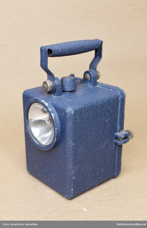 Førkrigsgjenstand, brukt om bord i båt.  Man hadde pax Firkantet lykt med håndtak og bryter på toppen. Lyktekassen er blålakkert med hammerlakk. Et rundt glass foran på lykta, gir vanlig hvitt lys. En blank reflektor bak pæra og glasset samler lyset i en retning. Bak er et mindre firkantet rødt prismedelt glass for rødt lys. Lyktekassen har stor plass til batteri. Batteriet kan skyves inn fra baksiden der hele veggen kan åpnes med maskinskruer.
