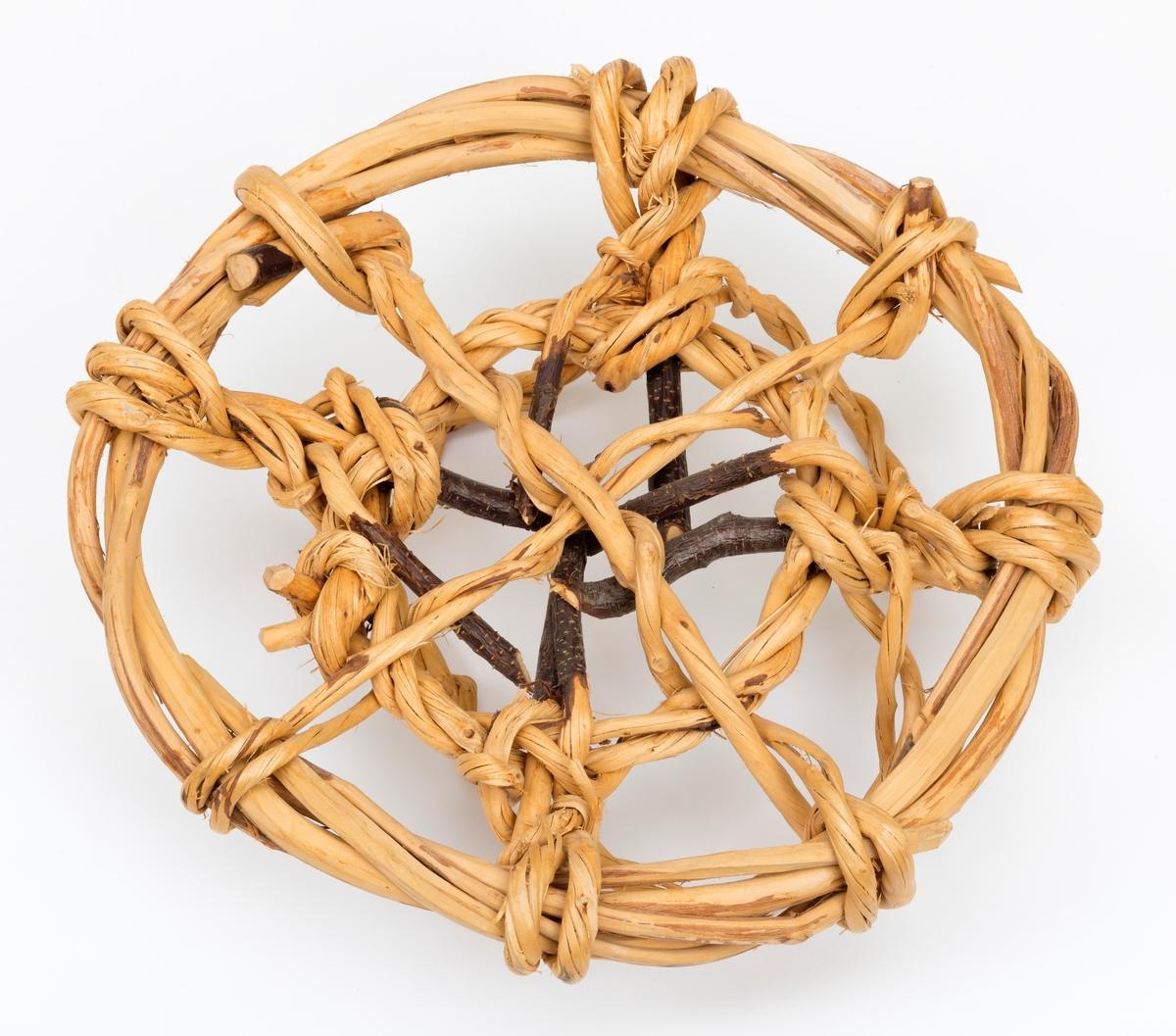 Materialet i trugene er bjørk. De er ubrukte. Ringen er satt sammen av fire grener, mens flettverket i bunnen og de fire hempene til å feste på hestebeinet er laget av vidjer.