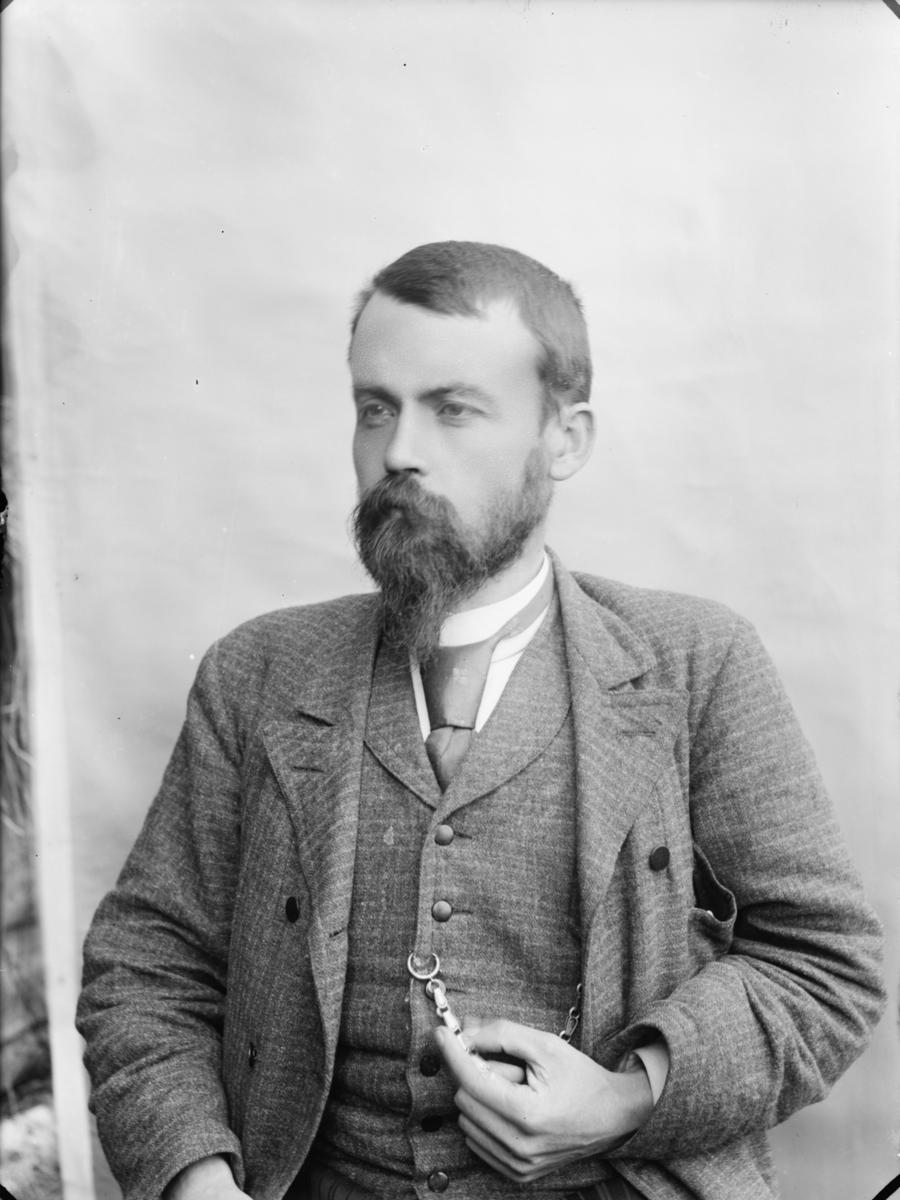 Mann med sjegg i vest og jakke, portrett.