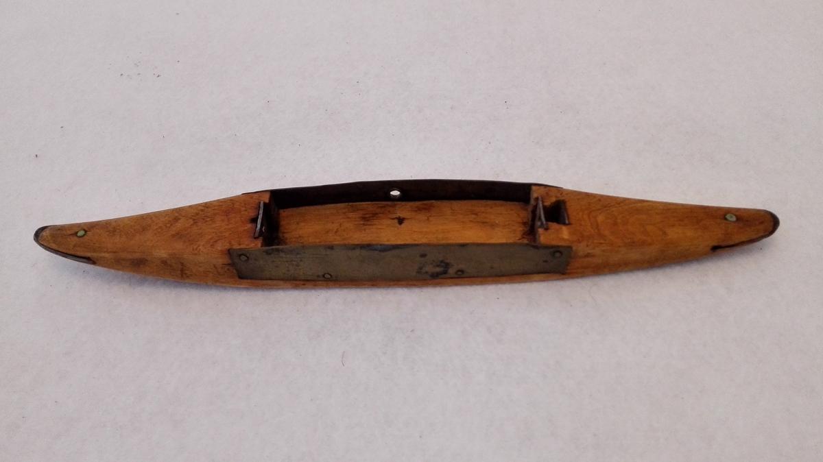 3 vevskutler (14217 - 19)  14219 - Vevskuttel av bjerk. Lys brun beiset. På siderne av spjolerummet påslått messingplate og i enderne av samme innfelt firkantete jernplater med hul for spjolepinderne. Længde 26,2 cm. Skuttelen har i enderne innfelt jernspisser.  Kjöpt på Lærdal av Durdei Johannesen (Abrahams Durdei).