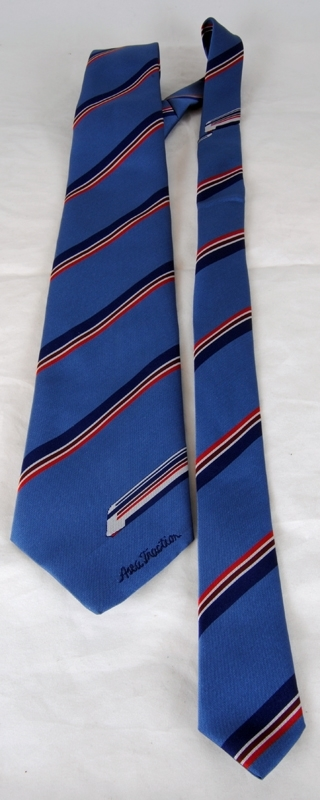 """Blågrå slips med ränder i rött, vinrött, vitt och mörkblått. Längst ned föreställer ränderna ett tåg, troligtvis ett X 2000, samma mönster finns längre upp på slipsen. Längst ned finns texten: """"Asea Traction"""", maskinbroderat i mörkblått. På insidan finns en mörkblå textillapp med texten: """"SPECIALLY MADE FOR ASEA TRACTION BY PEER OF SWEDEN"""", samt tvättråd."""