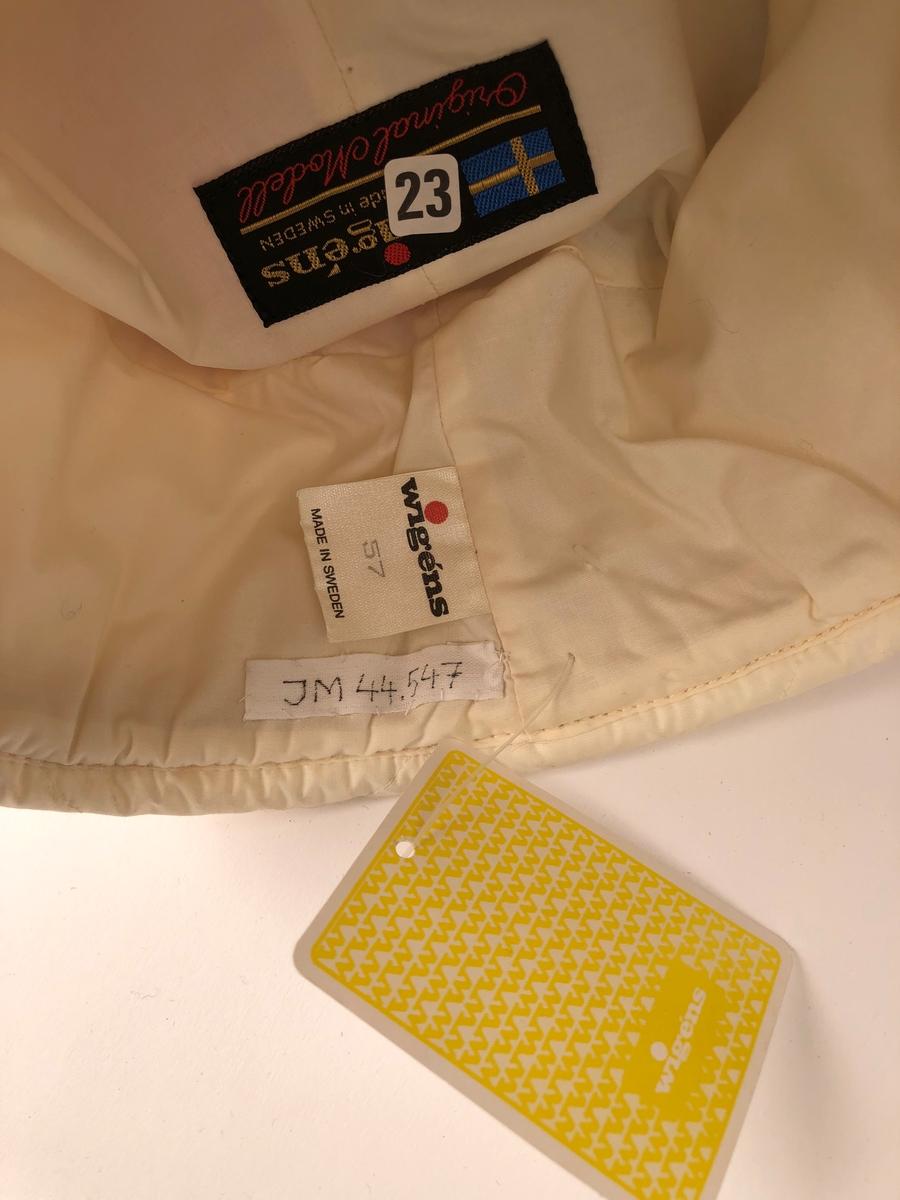 """En så kallad skidmössa i qviltat tyg med vit skärm, kullen är tvåfärgad: vänster sida svart, höger röd, dessa fält går ner mot skärmen. Sidorna är av vitt qviltat tyg, uppfällda öronlapper är uppfästade med tryckknappar på vardera sida. Mitt fram sitter ett beige märke med text: """"wigéns"""".  Mössan har vitt foder, på vilket är fastsytt en svart etikett med gul text: """"wigéns MADE IN SWEDEN"""", och röd text: """"Original Modell"""" samt svenska flaggan. Ytterligare en etikett anger storlek """"wigéns 57 MADE IN SWEDEN"""". Inuti mössan sitter även en klisterlapp märkt: """"23"""". En vidhängd pappersetikett är märkt: """"240""""."""