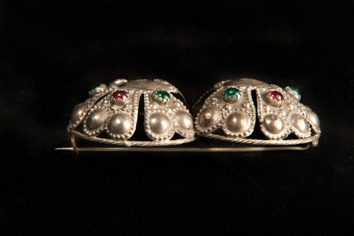 Ett par hoptvinnade maljor av ciselerat och delvis genombrutet silver med dekor av prickar. Tio infattade små stenar av glas (fyra röda och sex gröna).  Spännet, maljan, har gjorts om till en brosch. Något otydliga stämplar.