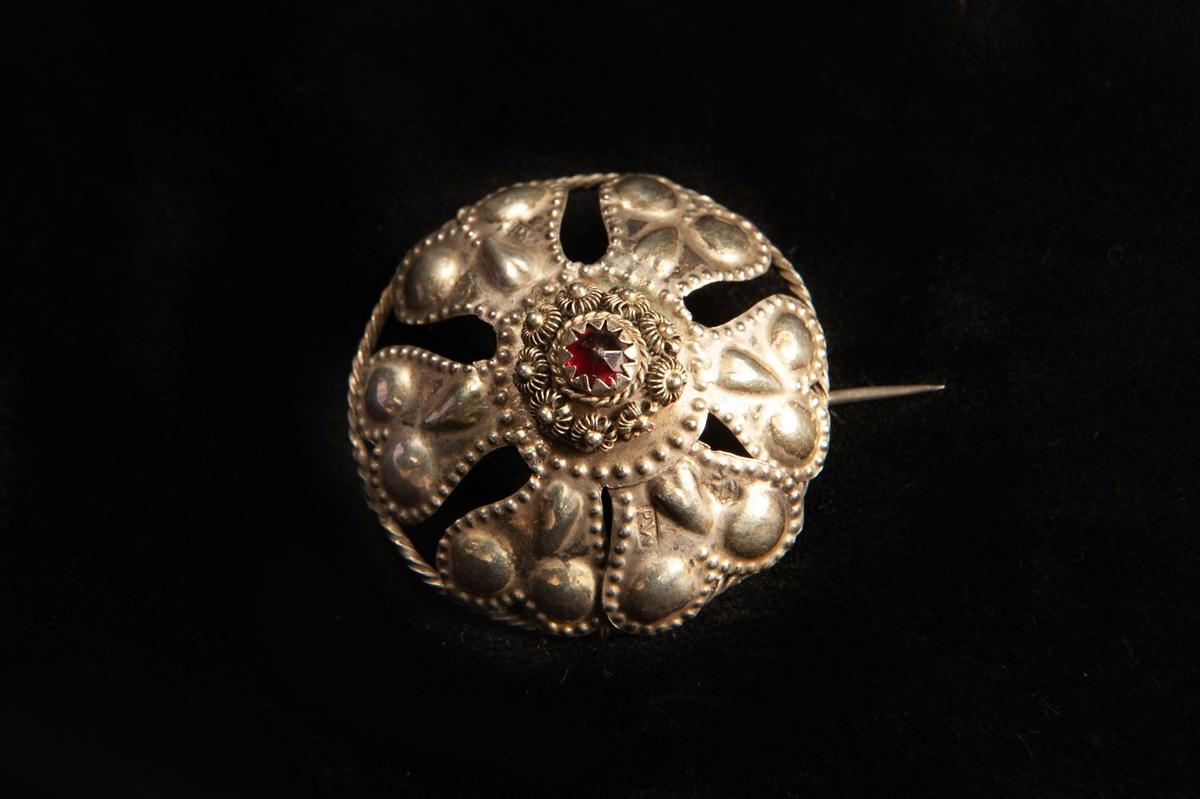 En rund malja av ciselerat silver med utseendet av hjärtformade blomblad kringen en infattad röd sten av glas. Runt stenen filigranarbete. Spännet, maljan, har gjorts om till en brosch.