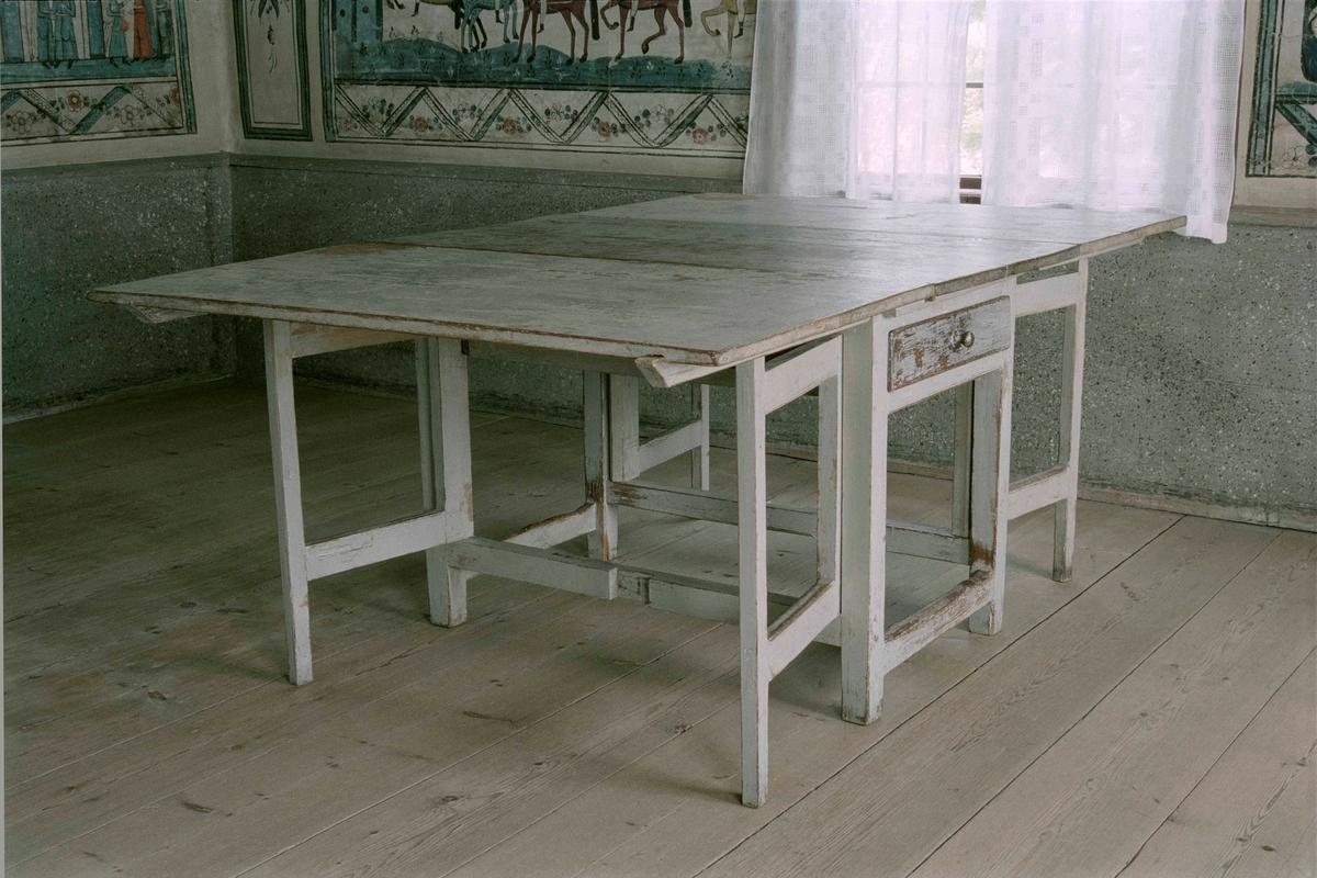 Slagbord av trä, fast rektangulär skiva, i sargen en låda i var kortsida, 2 fällbara skivor med 2 grindar under varje, tvärslå. Målad gråblå, färgen kraftigt nött på fasta skivan.