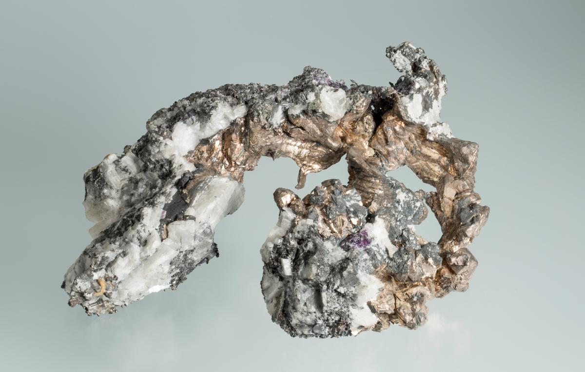 """Gammel etikett: 280 Vekt 2025,71 Størrelse: 19,5 x 14 x 5 cm Beskrivelse fra plakat i ramme: """"41. Kongens gruve 1916. Tykt trådsølv med krystallflater. Enkelte sølvhorn. Rester med sulfidovertrekk. Tagget basis i kvarts. Påsittende klase av sølvkrystaller""""."""