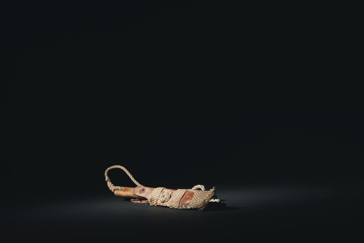 Kniv med rakt blad. Handtag av trä fäst i bladet med två genomgående nitar. I skaftet har brukaren ristat in skåror, skårorna ska enligt uppgift ha olika betydelser. Brukaren förvärvar rätten att skära in en skåra i skaftet vid olika händelser i hans sjömansliv.  I skaftet har brukaren även ristat in en neptungaffel och ett kors.   Överst i skaftet ett hål klätt med metall. I hålet sitter ett snöre med en ögonsplits som förbinder kniven med slidan.   Slidan är av läder. I nedre delen sitter makramé inflätat i platting. Nära toppen två valknopar, en på varje sida.