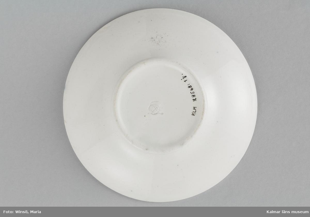 KLM 28568:1:1-13. Dockservis, teservis, flintporslin. Vitt gods, alla ytor, med undantag för tefatens undersidor, med grålila marmordekor under klar, ofärgad glasyr. I fatens undersida en intryckt stämpel, har ej kunnat bestämmas.  :1:1 Tekanna, svag vertikal kannelering, låg, vid bukig, indragen omedelbart ovanför fotkanten, mynningspartiet vinklat och med obetydlig snedställd 1,7 cm bred översida, fals för locket, örat volutformigt, ca 2,5 cm högre än kannan i övrigt. höjd 8 cm (10,3 cm), största diameter 9,5 cm, övre diameter 8,7 cm, botten diameter 6,4 cm.  :1:2 Lock, välvt, till kannan, med svagt markerad, strålform, kannelering, knopp i form av blomma med fyra svagt räfflade kronblad, genomborrat m runt hål inuti knoppen; försett med fals. Höjd 2,8 cm, diameter 5,3, falsens diameter 3,8 cm.  :1:3 Sockerskål, form som :1:1, två tvärställda öron diameter 2,9 cm, det ena avslaget, locket saknas. Höjd 6,2 cm, största diameter 9,5 cm, övre diameter 8,3 cm, botten diameter 6,8 cm. :1:4-8 Koppar, 5 st, skålformiga med kraftig indragning ovanför fotkanten, bottenytan nedsänkt ca 6 mm, smalt ögleformigt öra med stödten på mitten. :1:7 har örats övre del avslagen. Höjd 4,8 övre diameter 7,4 cm, botten diameter 3,8 cm.  :1:9-13 Tefat, 5 st varav 1 st lagat (6 bitar), ett fat med svagt missfärgad glasyr, obetydliga glasyrsprickor. Släta med kanten skålformigt vidgad, markerad försänkning i botten, undersidan svagt försänkt med instämplat märke. Höjd 2,2 cm, övre diameter 11,7 cm, botten diameter 5,7 cm.
