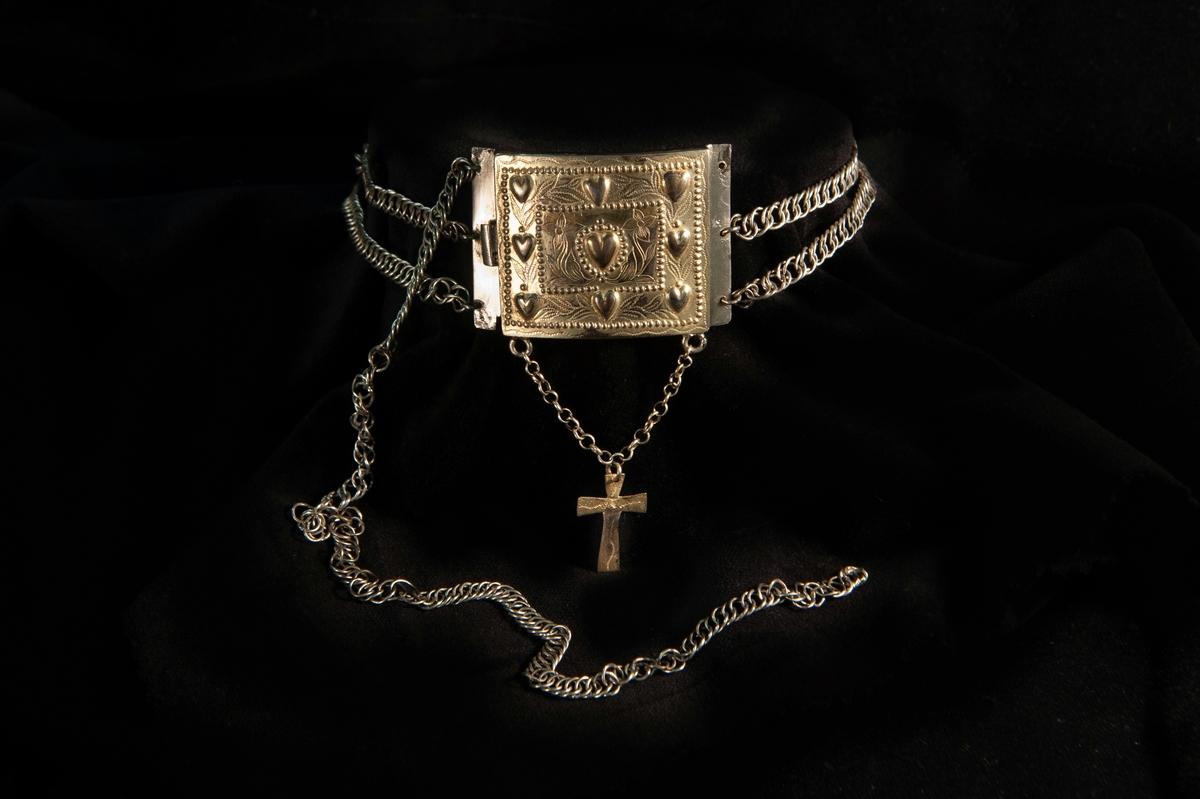 Ett s.k. halslås i delvis förgyllt silver. Förgylld frontplåt med dekor i form av ciselerade hjärtan och graverade blommor. Undertill ett förgyllt och graverat kors av silver i ankarkedja. Dessutom är låset försett med tre pansarkedjor.
