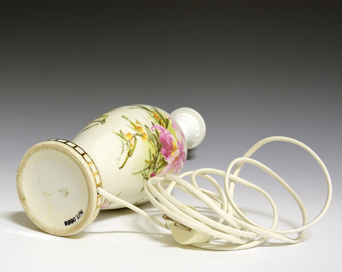 Lampefot av porselen, slank, glatt med lang halsog innsnevring mot foten. Hvit glasur. Med uoriginal lampeskjerm og ledning. Finner ikke modellen i priskuranten. Bunttrykkdekor med blomstermotiv.