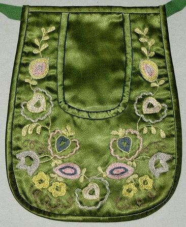 Hedemora kjoväska i grönt siden med kedjestygnsbroderi.Broderiet domineras av färgerna gult och rosa. Baksida av grönt bomullstyg + foder av bomull. Ett 100 cm långt bomullsband i grönt.Bandet är fastsytt i båda hörnen.