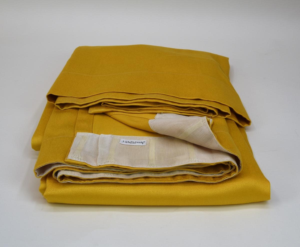 En gardin av gult siden, ihopsydd på mitten av två delar. Gardinen har fåll nedtill och upptill i form av  vitt bomullstyg med plats för 37 stycken hängare.