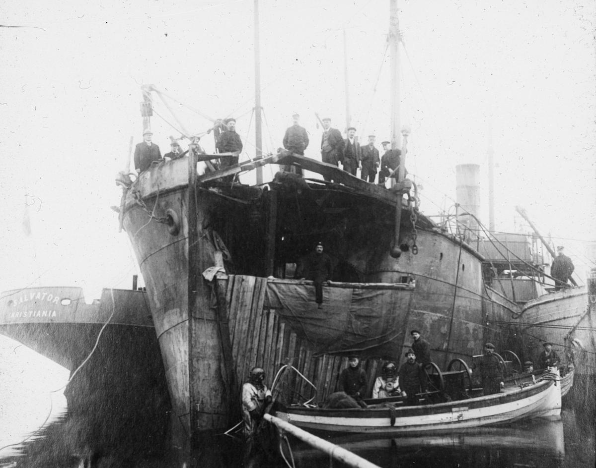 Arbeidsfolk ombord på fartøy med stor flerre i baugen. Til venstre fartøy merket SALVATOR- Kristiania. I forkant lettbåt med to hjelmdykkere, to luftpumper og 6 mann til.