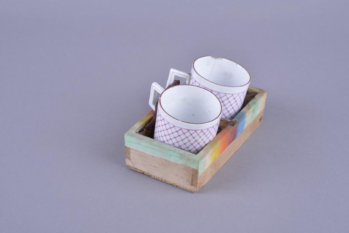 En kopp i hvit porselen, dekorert med rosa ruter. Koppen er festet med et tynt bånd (kan se ut som en skolisse), som er spikret fast i skrinet (FTT.TSM.2515) med en liten spiker. Koppen er festet sammen med enda en identisk kopp i samme størrelse. Koppen virker håndlaget, og er nokså skjør.